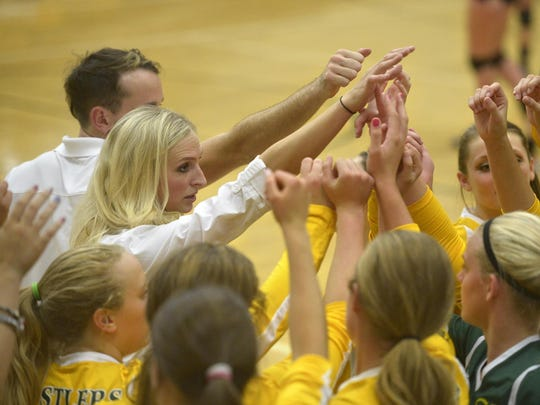 CMR head volleyball coach Theresa Besich, left, huddles with her team during a timeout in the Rustlers' match against Missoula Big Sky in the CMR Fieldhouse.