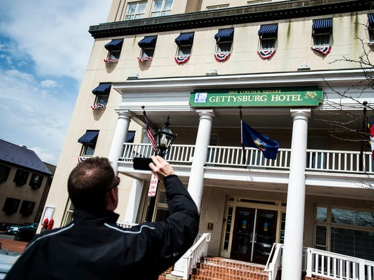 Jim Walski, a visitor from California, takes a photo of the Gettysburg Hotel.