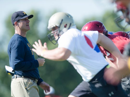 Michigan football coach Jim Harbaugh looks on during the Coach Jim Harbaugh's Elite Summer Football Camp, Friday, June 5, 2015, at Prattville High School in Prattville, Ala.