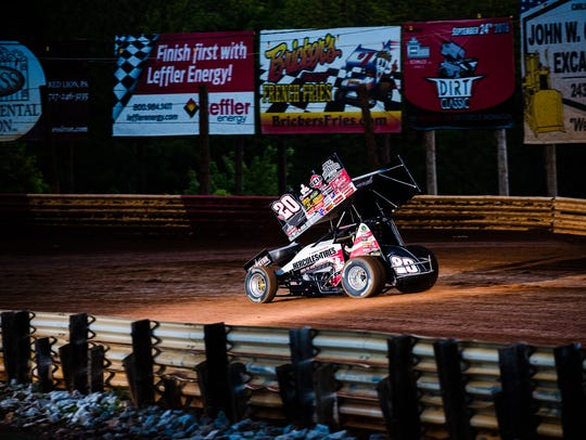 A flash from a camera illuminates the sprint car of driver Greg Wilson during a race in May 2016 at Lincoln Speedway as the World of Outlaws competed against the PA Posse. Wilson will be making an appearance at Eagle Tire in Milton on Wednesday.