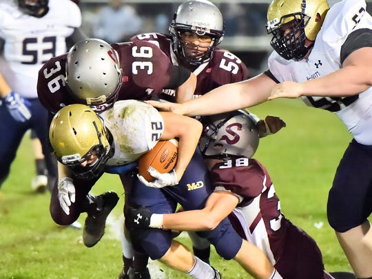 Shippensburg defenders Ian King (36), Denny Santana-Encarnacion (59) and Eddie Ocker (38) bring down Matt Geiger (22) of Bishop McDevitt during a District 3 Class 4A football semifinal game on Friday, Nov. 18, 2016. The Greyhounds pulled out a 29-28 win, despite Geiger gaining 242 yards rushing.