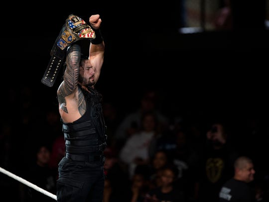 Roman Reigns holds up the United States Champion belt