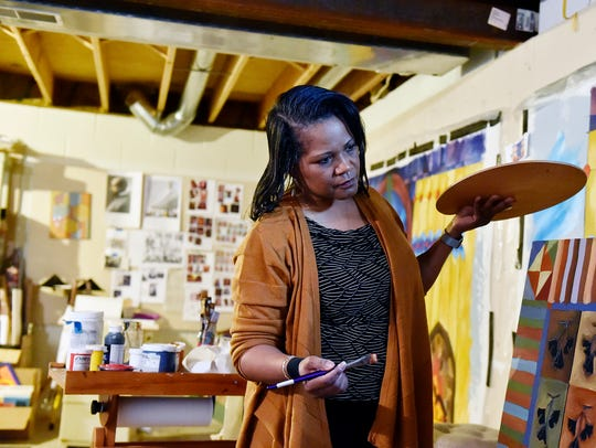 Ophelia M. Chambliss works on a painting Tuesday, March