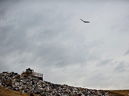 A city employee works to bury trash at the city landfill