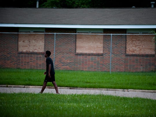 A pedestrian walks in front of a boarded up house in