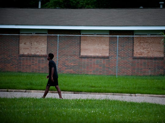 A pedestrian walks in front of a boarded up house in Smiley Court on Tuesday, June 6, 2017, in Montgomery, Ala.