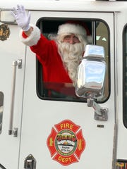 Santa Claus rode into the Deming Kmart on Saturday in a Deming Fire Department ladder truck and was greeted by 351 children and their families for the annual Shop With a Cop.