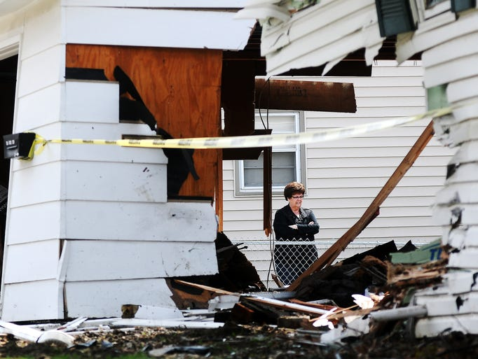 Theresa Hay checks out the damage to her next-door-neighbor's house  on the 2300 block of South Blauvelt Avenue after a vehicle drove through part of the house and the garage on Thursday, April 24, 2014, in Sioux Falls. (Joe Ahlquist / Argus Leader)