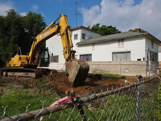A back hoe works on the clean-up phase of the remains at 1702 West Kentucky Street after a home designated as an emergency demolition was taken down by National Environmental Contracting. June 12, 2014