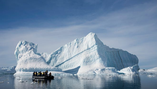 An inflatable boat carries tourists past an iceberg in Antarctica.