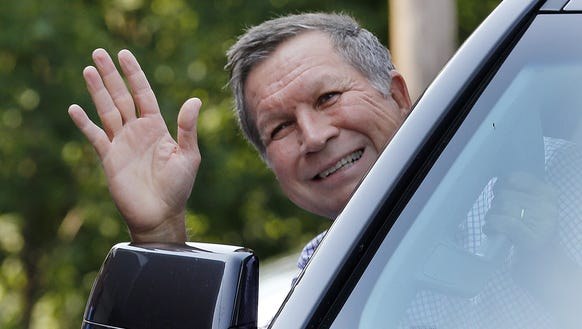 John Kasich waves as he arrives for a campaign stop