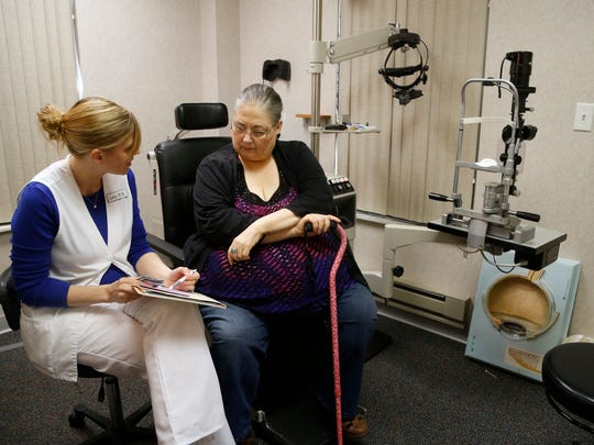 Karen Slessor, right, listens as registered nurse Lacy Kolder goes over her prescriptions from the doctor Wednesday, May 3, 2017, during an appointment at Wolfe Eye Clinic in Cedar Falls, Iowa. Slessor is worried she may lose her last insurance option if Medica pulls out of Iowa's individual health insurance market.