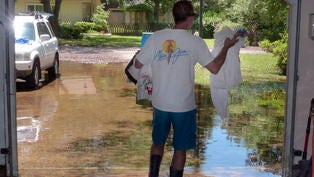 Gary Petersen who lives on Whisper Oaks Drive in the Whisper Bay subdivision removes items from his flooded garage as he tries to cleanup flood damage even as flood water still surround his house on Saturday, four days after heavy rains caused widespread damage in the Pensacola area.