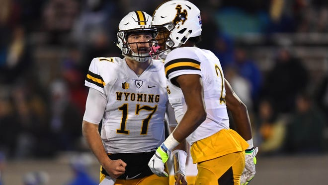 Wyoming quarterback Josh Allen celebrates with receiver Jared Scott after a touchdown pass during Saturday night's game at Air Force. The win moved Wyoming up to No. 2 this week in our Mountain West power rankings.