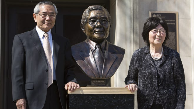 Nobel laureate  and Purdue University professor Ei-ichi Negishi with his wife, Sumire, pose after the unveiling of a bronze sculpture of him on April 18, 2014, outside of  Wetherill Laboratory of Chemistry on campus at  Purdue University in West Lafayette.