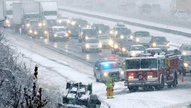 A over-turned automobile on Interstate 84 snarls traffic, Wednesday, Nov. 26, 2014 in Vernon, Conn.  The National Weather Service has issued a winter storm warning, calling for snow during the day on Wednesday, changing to rain and snow in the evening with rain and snow showers possible on Thanksgiving day.