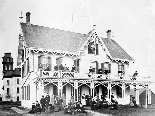 An early photo shows students and faculty in front of the 1857 Stearns House, the first building at what ultimately became St. Cloud State University. Old Main, erected in 1874, stands behind.