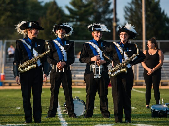 The Littlestown Marching Blue Band members wait to perform for the Littlestown Thunderbolts football team's entrance onto the field.