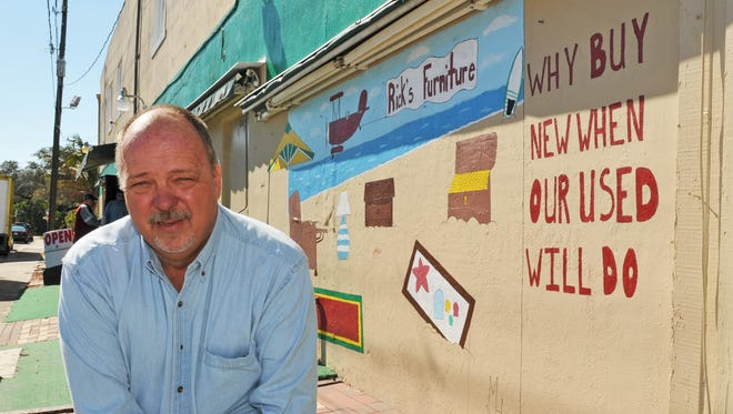 Rick Hester stands in front of a mural painted by his daughter outside his business, Rick's Furniture & Consignment Sales, in Eau Gallie.