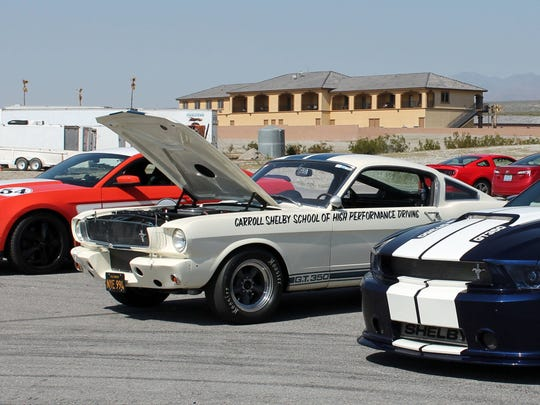 A 2012 Ford Mustang Boss 302, a 1965 Shelby GT350, and a 2013 Shelby GT350 convertible wait their turn on the track during the 6th annual Shelby Bash at Spring Mountain Motorsports Ranch in Pahrump, Nevada.