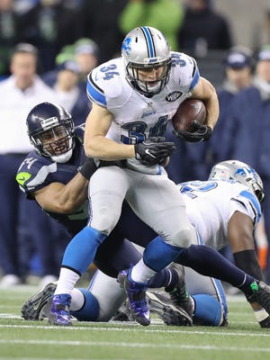 Detroit Lions runningback Zach Zenner is tackled by Seattle Seahawks linebacker Bobby Wagner during the second quarter  of the playoff game on Saturday in Seattle.