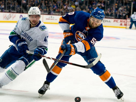 New York Islanders' Adam Pelech battles the Vancouver Canucks' Sven Baertschi for the puck during the first period of an NHL hockey game Tuesday, Nov. 28, 2017, in New York. (AP Photo/Craig Ruttle)