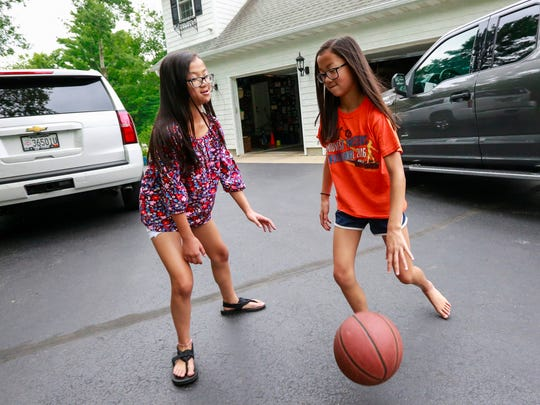 Gracie Rainsberry, left, and her twin sister Audrey Doering play a basketball game Wednesday, July 25, 2018, the Doerings' house in Wausau, Wis.