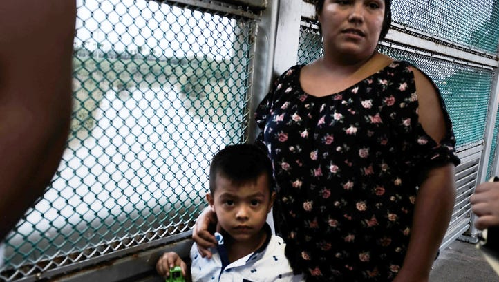 A Mexican woman and her child are held up by the border