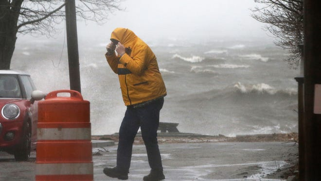 A pedestrian walks near the coastline in Newburyport, Mass. as a major nor'easter pounds the East Coast, packing heavy rain, intermittent snow and strong winds.