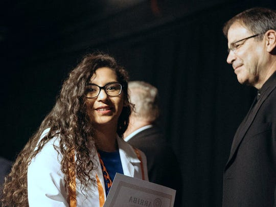 Maria Aguilera was one of 66 graduates honored at Project Arriba's 33rd graduation ceremony in May. She received a nursing degree from UTEP in May. Looking on is Father Ed Roden-Lucero, Project Arriba vice chairman.