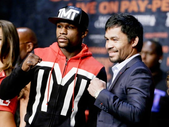 Boxers Floyd Mayweather Jr., left, and Manny Pacquiao pose for photographers during a press conference Wednesday, April 29, 2015, in Las Vegas. The pair are slated to square off Saturday in Las Vegas.  (AP Photo/Chris Carlson)