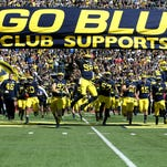 Michigan quarterback Devin Gardner (98) leads his team under the banner before a game against Miami University in Ann Arbor on Sept. 13, 2014.
