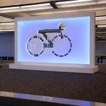 Cycle-inspired creations are installed on top of the baggage carousels in DIA's Jeppesen Terminal.