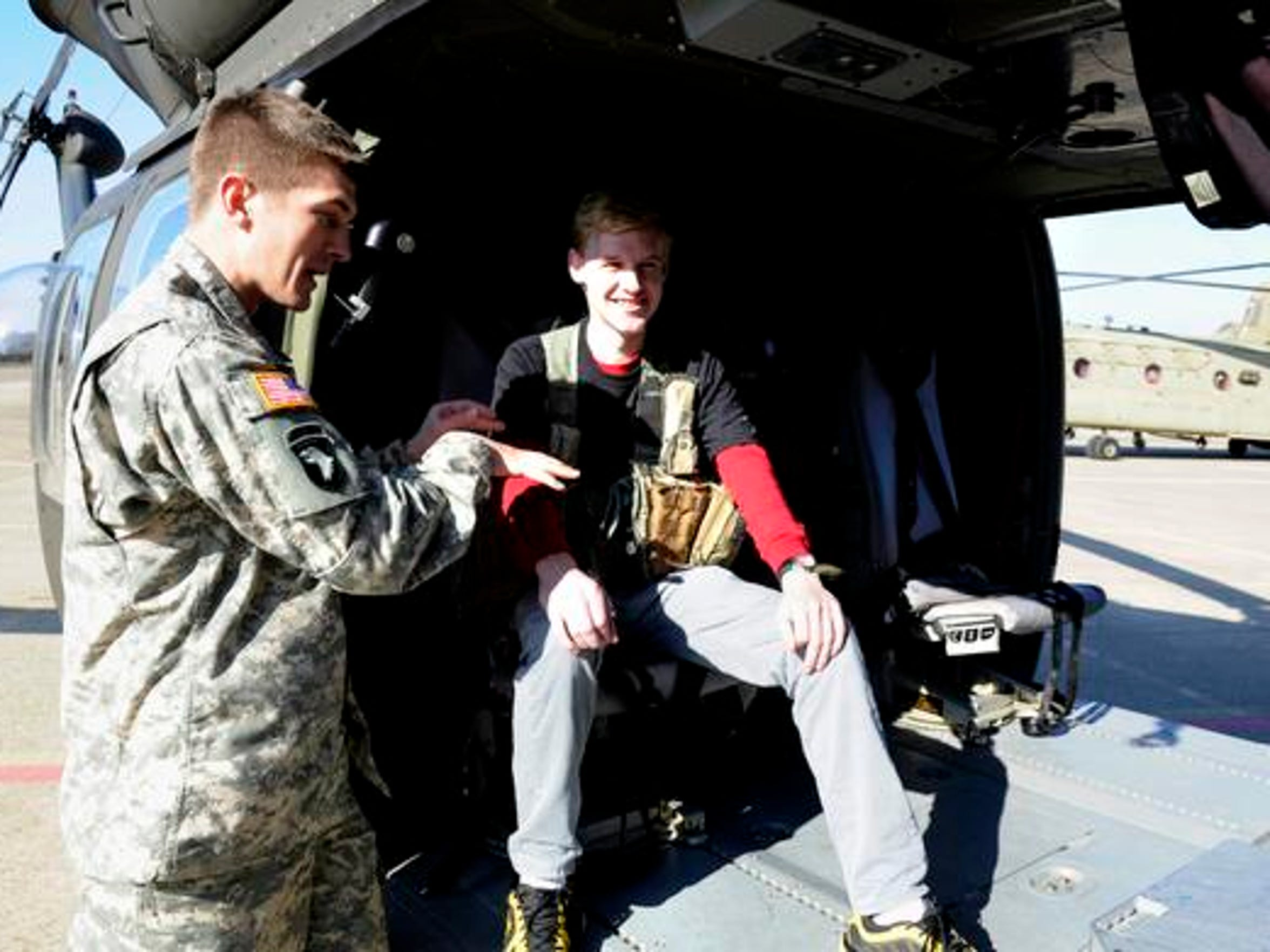 Army medic Andrew Six gives Jack Zimmerman a inside tour of a Black Hawk helicopter during Zimmerman's Make a Wish request which 2nd Squadron, 17th Cavalry Regiment, 101st Combat Aviation Brigade helped facilitate at Fort Campbell on Dec. 13, 2014.