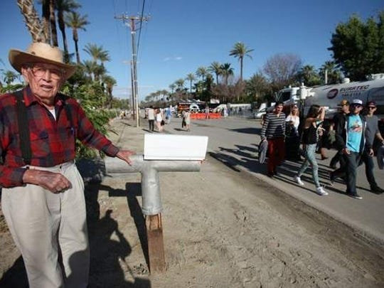 Roy Salazar of Indio stands at his mailbox with festivalgoers in the background in 2012.