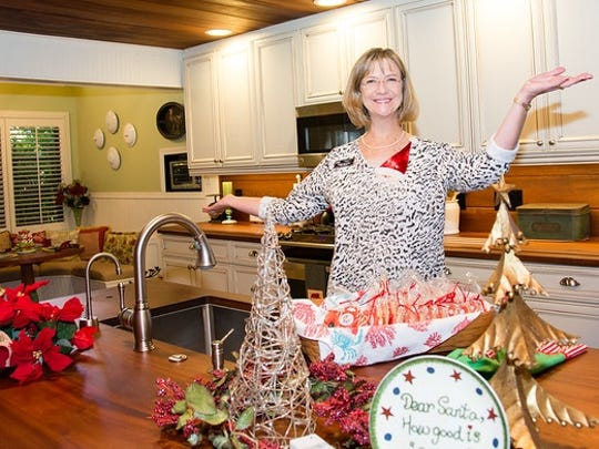 Holiday Home Tour home sponsor Adena Williams greets tour-goers with cookies.
