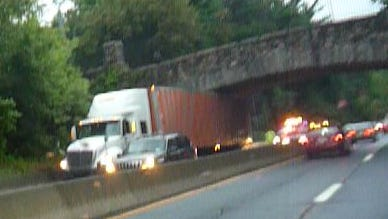 A tractor-trailer is wedged under the Weaver Street overpass on the northbound Hutchinson River Parkway, Sept. 27, 2016.