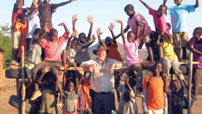 North Central State College assistant professor Ken Ekegren is surrounded by children from Malawi enjoying the playground he designed and built on a recent trip to Africa. It was later stolen.