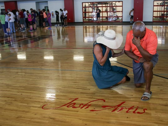 Peggy Artis, Josh Artis' stepmom, and his father, Mike Artis, react to the unveiling of Josh Artis' named on the court at Clarksville Athletic Club during a ceremony on Friday.
