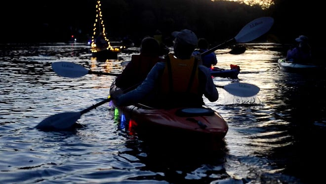 Supporters of Friends of the Winooski River paddle downstream to Lake Champlain Friday night, having decked kayaks and canoes with a bewitching array of lights.
