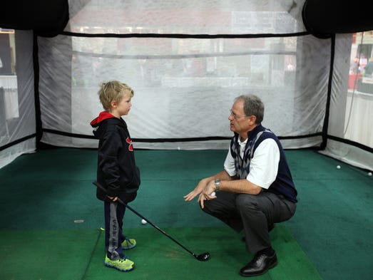 Max Galloway, head golf professional at Mohansic Golf Course in Yorktown Heights, gives Tommy Meagher, 6, of Pelham Manor some tips during the 10th annual Golf Show, March 8, 2014 at the Westchester County Center in White Plains. The show, sponsored by The Journal News, hosts nearly 75 exhibitors representing golf retailers, golf manufacturers, golf travel, instruction, and more.