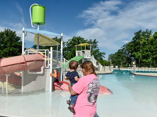 Charlene Auxier holds her 13-month old grandson Zander Adamson as he looks at the Lincoln Park Aquatic Center.