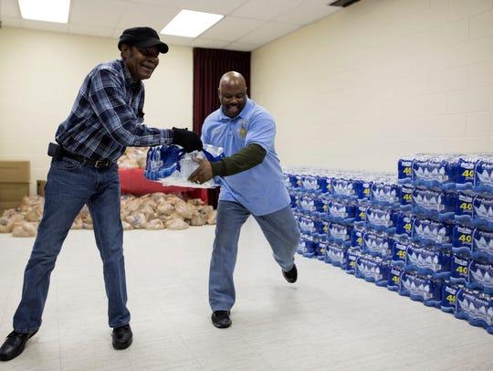 Eddie Fields of Flint, left, receives a case of water