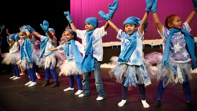 "Cast members raise their arms high during a rehearsal for the production of ""Frozen Fantasy"" Wednesday at the Eastside Boys & Girls Club. The performance will be Dec. 18th at 6:30 at the club and will feature four art forms taught under the Youth Arts Initiative."
