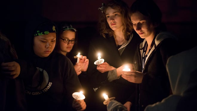 Community members light candles at a vigil for Douglas Bonham and Matthew Albrecht at Bethany Charter School in Silverton on Monday, March 7, 2016. Many students from Silverton High School, where Matthew Albrecht was a junior, attended the vigil, some wearing Seattle Seahawks gear or shirts honoring Albrecht's memory and his favorite sports team.