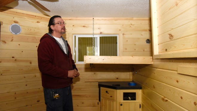 Custom Designed Innovations owner Tom Eizenhoefer lowers a custom bunk assembly in a ice house under construction Friday, Dec. 6, at his shop in Foley.