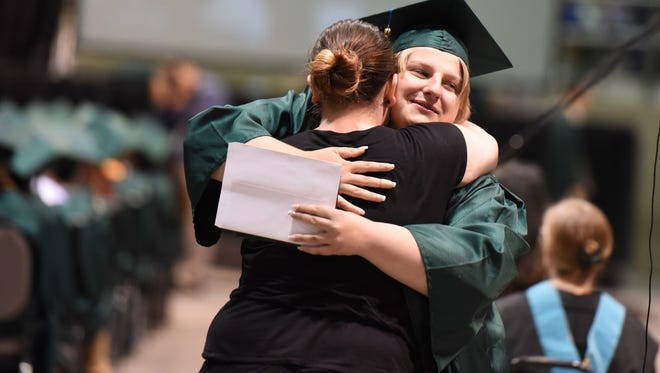 Graduate Gabriella Morrison embraces Alyshia Commins after receiving her diploma during the 38th annual Douglas McKay High School commencement on Friday, June 9, 2017, at the Oregon State Fairgrounds Pavilion.