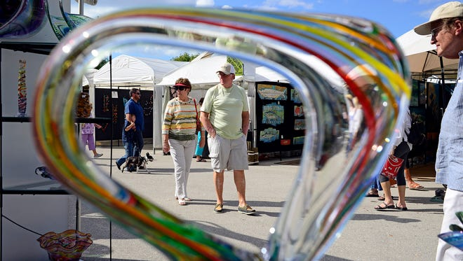 Donna Brilen, left, and her husband, James, both of Punta Gorda walk by the work of David Goldhagen Sunday, Nov. 16, 2014 at the bi-annual Art Show at the Miramar Outlet Mall in Estero, Fla. The two-day show drew thousands as they perused paintings, photos, sculpture, mixed media, jewelry, clothing and other artistic mediums. (Corey Perrine/Staff)