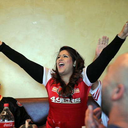 Ofie Perales celebrates a Broncos gain during the second quarter of Sunday's broadcast of Super Bowl 50 at the Pizza Factory on Boronda Road. Many of the members of Perales' church were San Francisco fans.