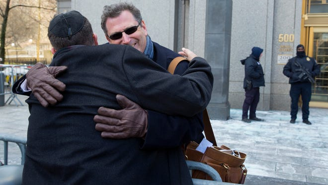 Attorney Kent Yalowitz, right, representing those affected by attacks in Israel in the early 2000s, hugs Mark Weiss of New York outside a federal courthouse in New York Monday, Feb. 23, 2015. The court found the Palestinian authorities liable in the attacks, with jurors awarding the victims $218.5 million in damages at a civil trial.